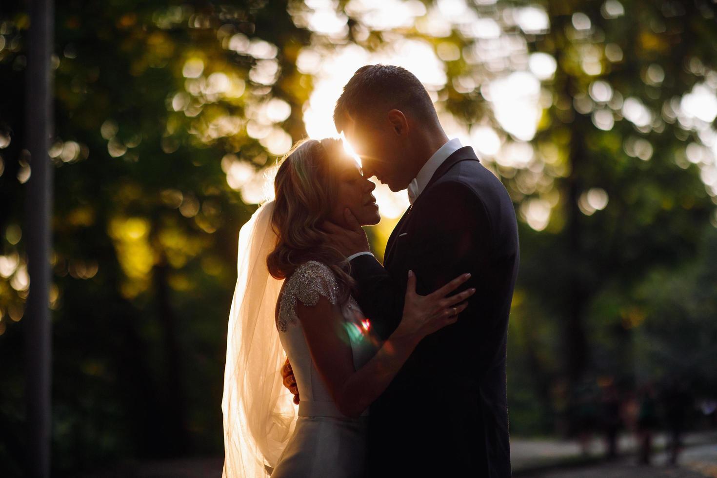 soleil d'été derrière un beau couple de mariage photo
