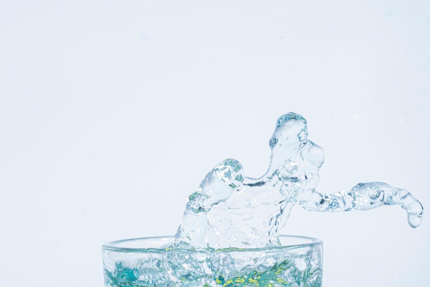 éclaboussure d'eau dans un verre sur fond blanc photo