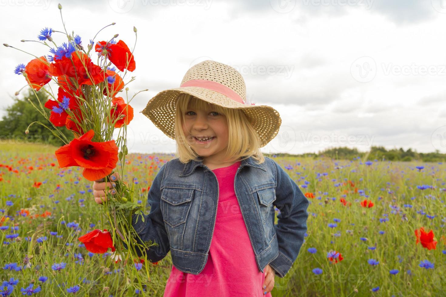 heureuse petite fille avec un bouquet de fleurs sauvages. photo