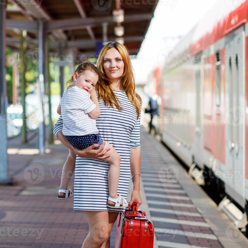 mignonne petite fille et mère sur une gare. photo