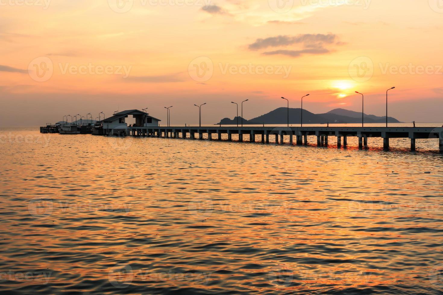coucher de soleil derrière un petit navire portuaire et un lampadaire photo