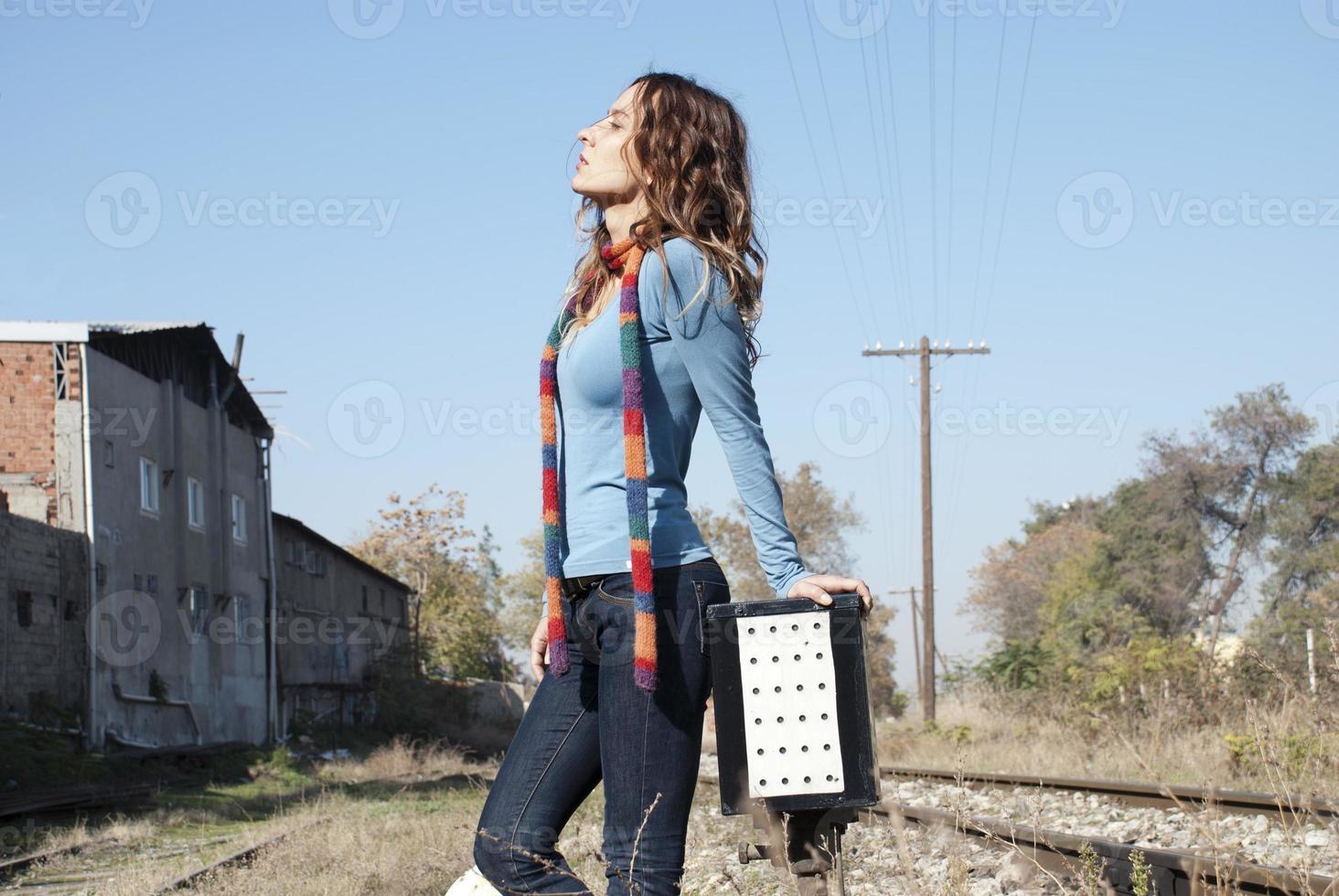 Jolie jeune femme posant sur une voie ferrée photo