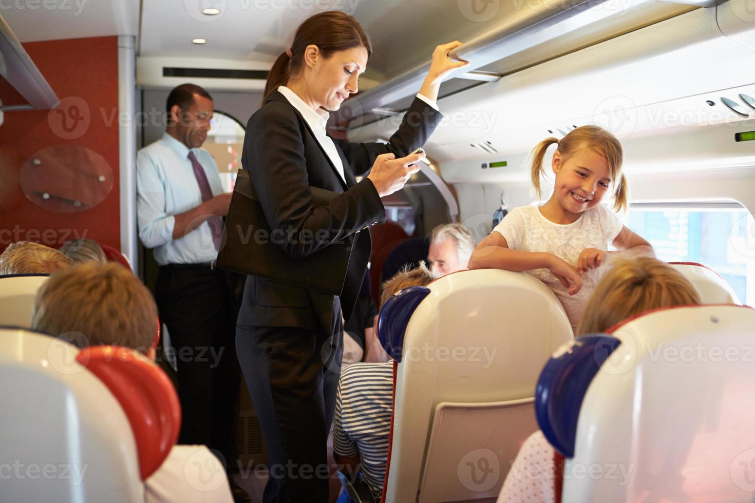 businesswoman using mobile phone on train de banlieue occupé photo