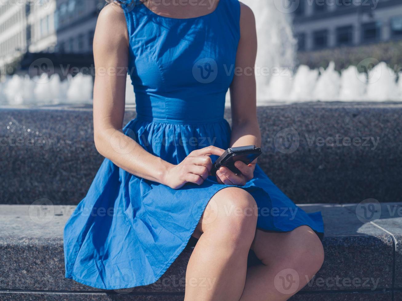 jeune femme, utilisation, téléphone intelligent, par, fontaine, dans, ville photo