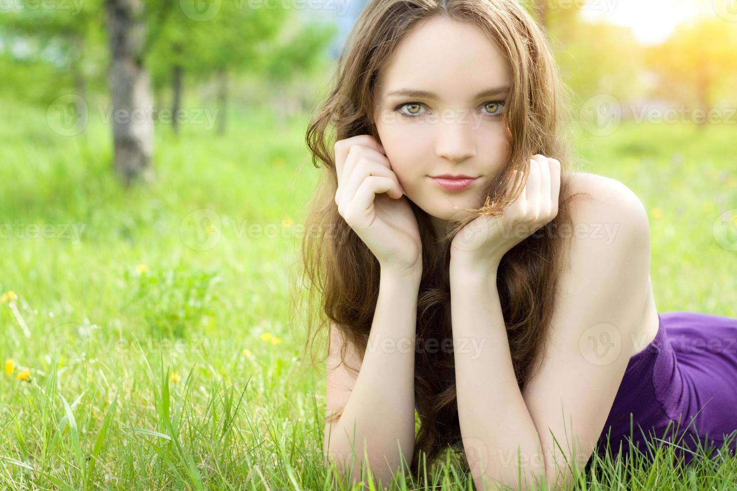 jeune fille adolescente brune allongée sur le pré photo