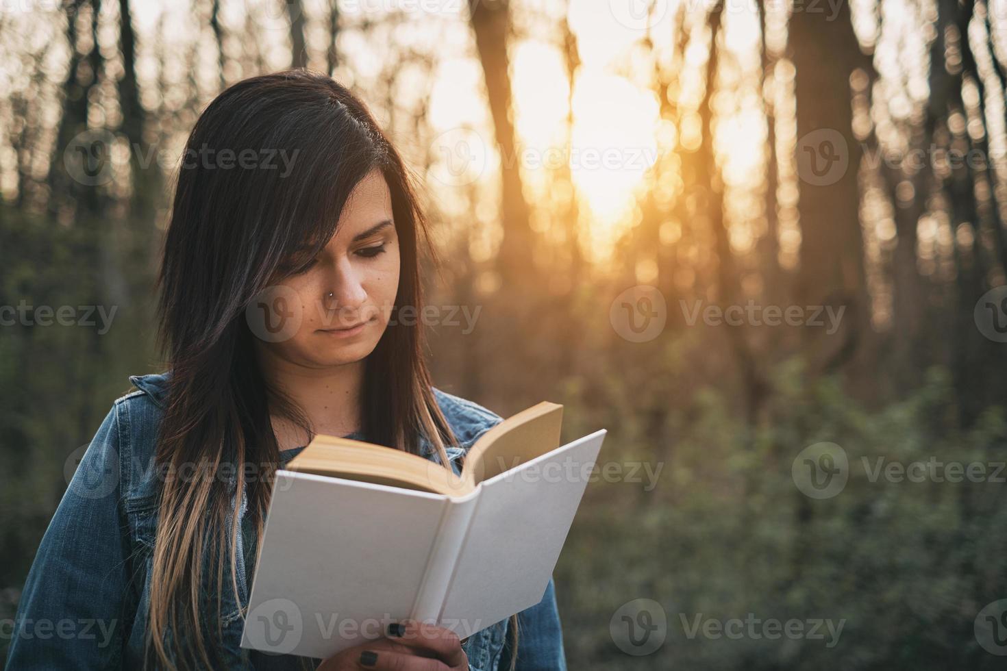 jeune fille lisant livre en plein air photo