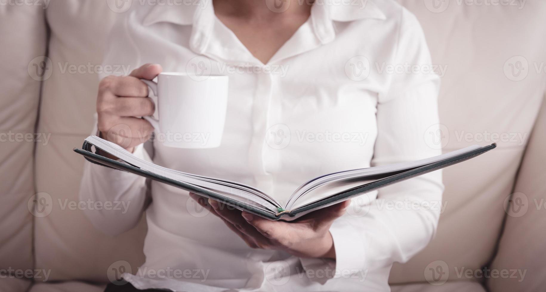femme assise sur un canapé et livre de lecture avec tasse photo