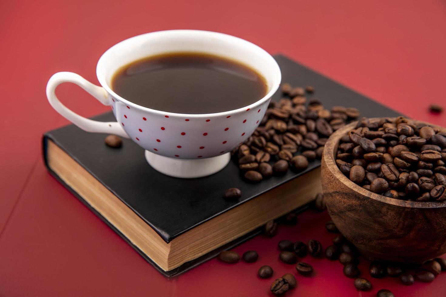 Vue de dessus d'une tasse de café avec des grains de café isolé sur fond rouge photo