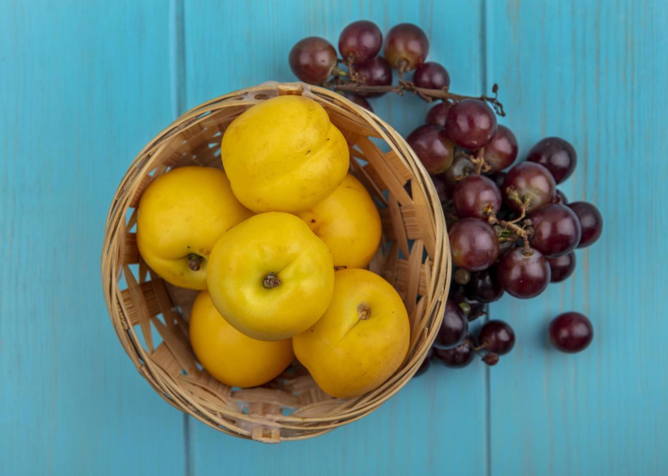 Assortiment de fruits dans un panier sur fond bleu photo