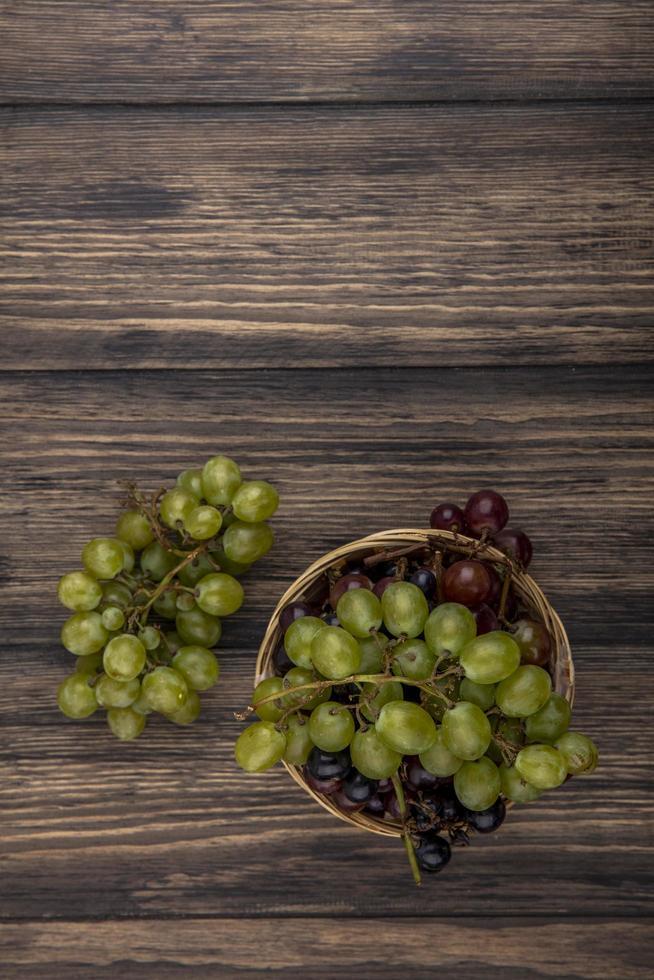 Vue de dessus des raisins dans le panier et sur fond de bois avec espace copie photo