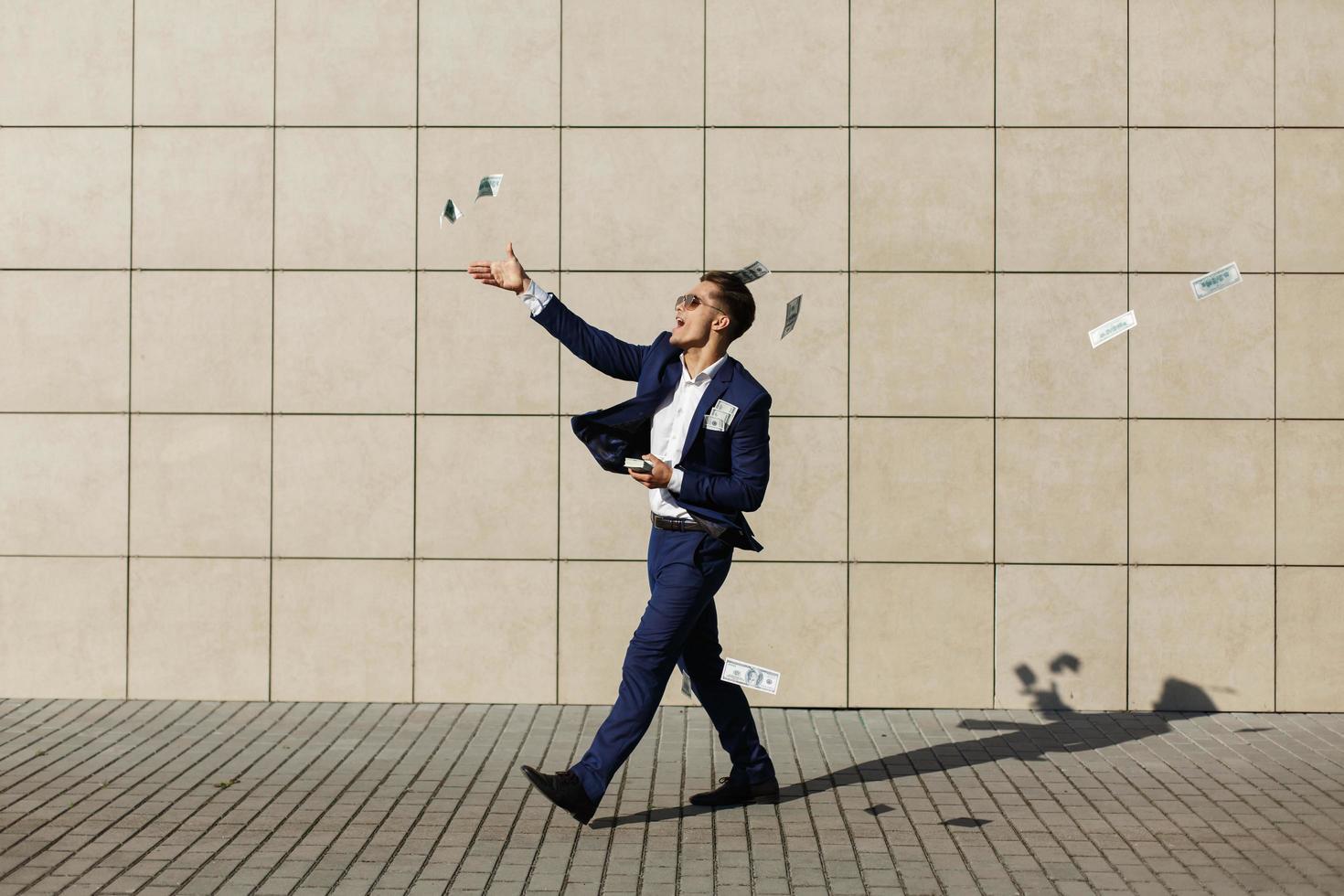 un jeune homme dansant avec de l'argent dans la rue photo