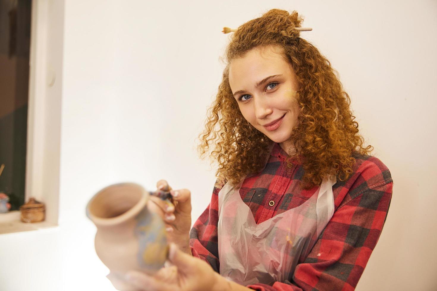 Jolie fille aux cheveux bouclés souriant tout en peignant un vase photo