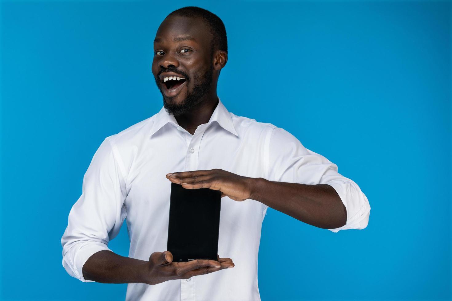 homme mignon sourit et tient une tablette photo
