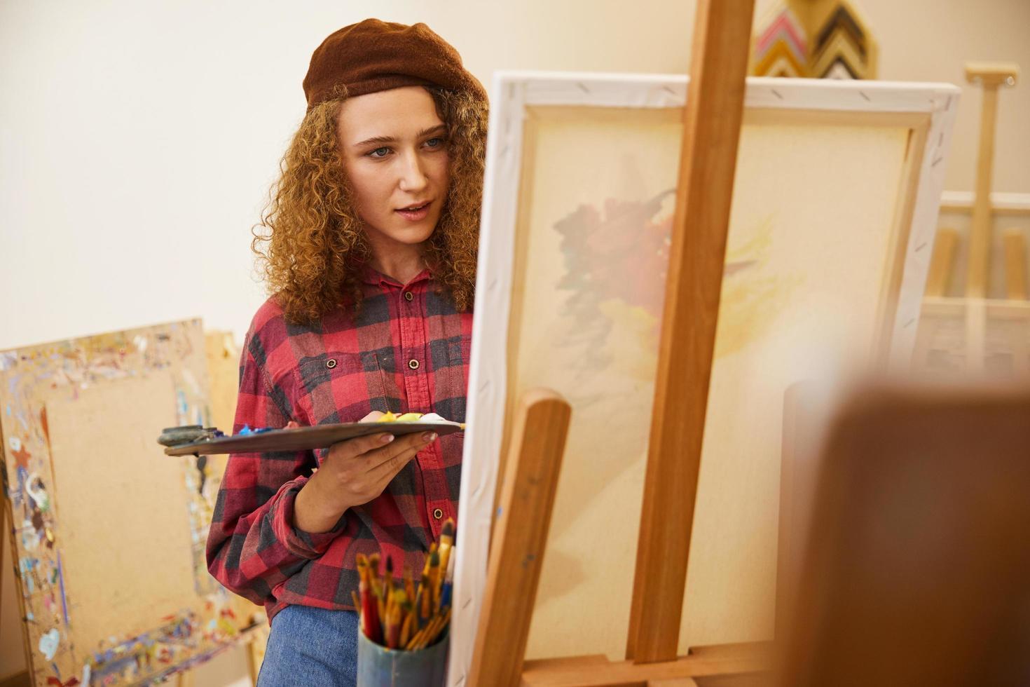 fille dessine une image avec des peintures à l'huile et un pinceau photo