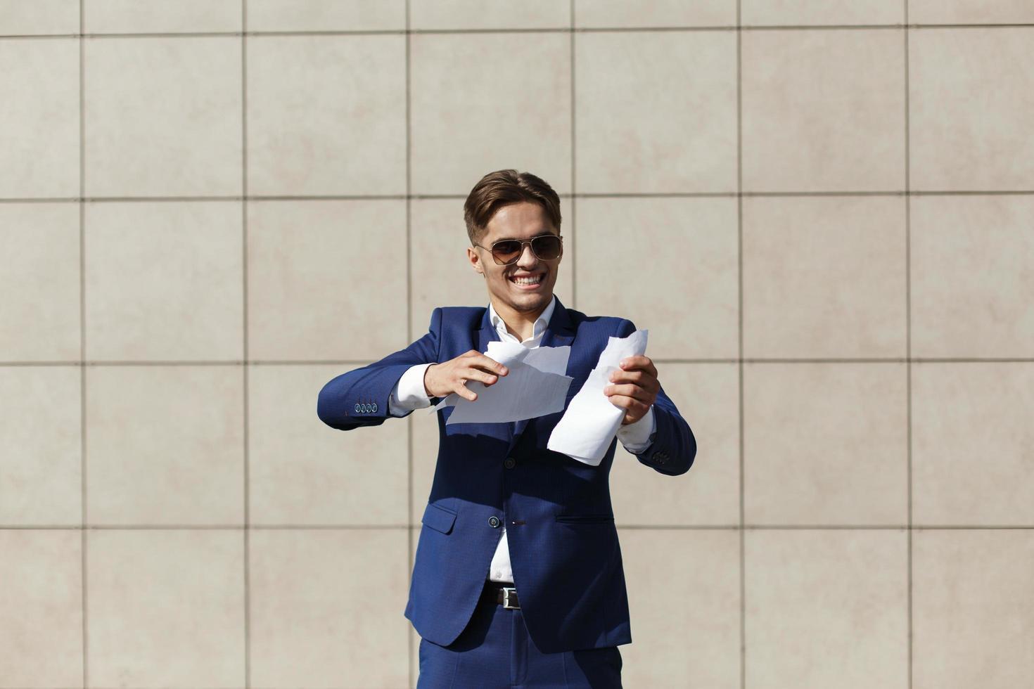 un jeune homme d & # 39; affaires déchirant un morceau de papier photo