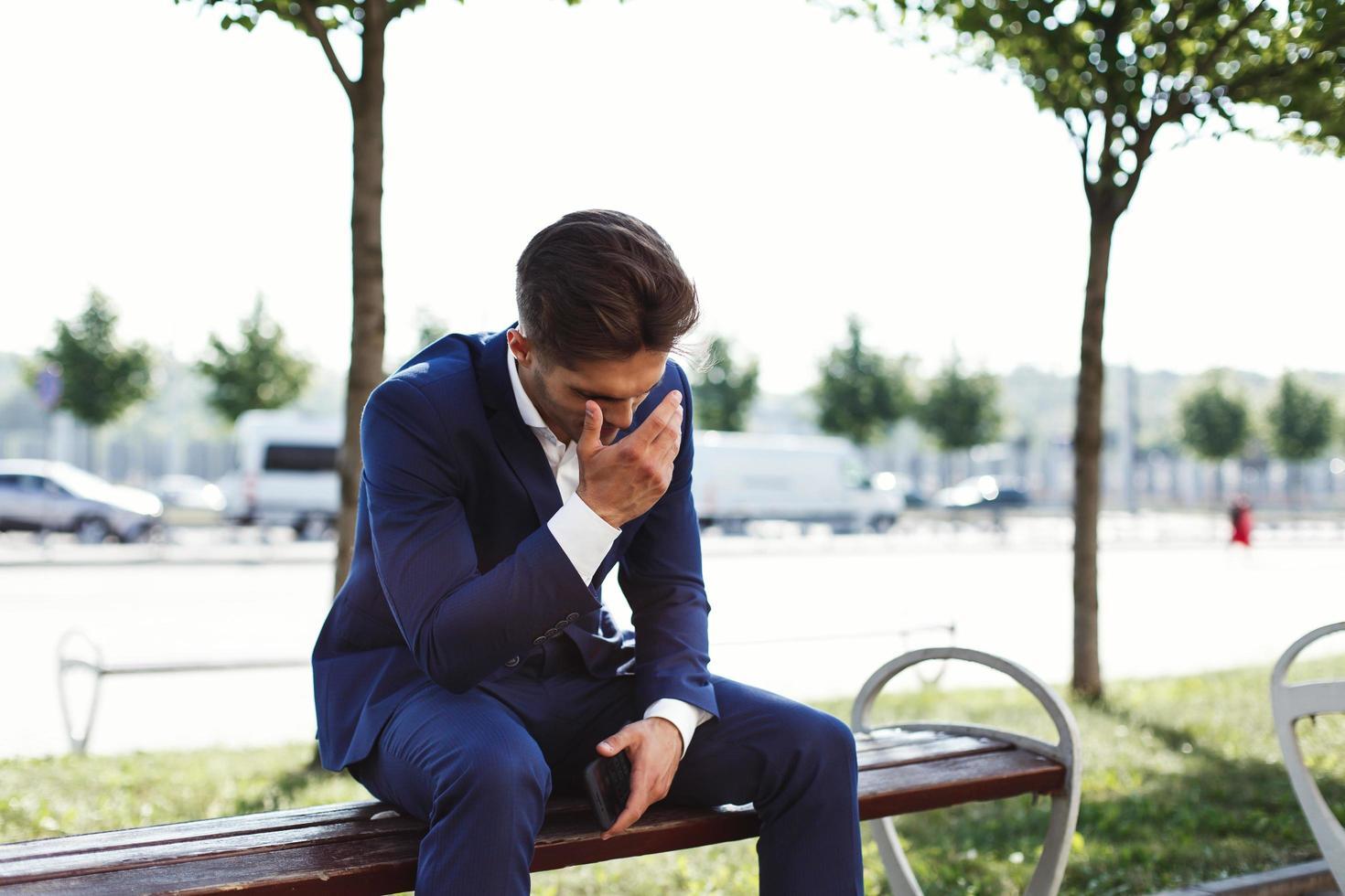 homme d'affaires triste est assis à l'extérieur de la rue photo