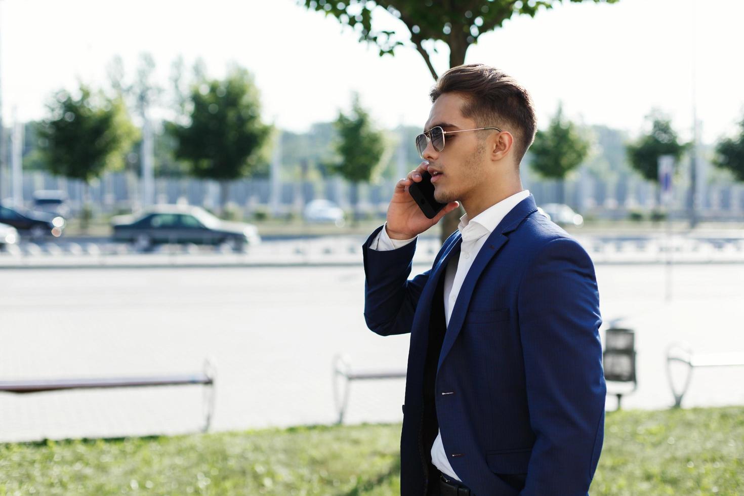 homme en costume marchant et parlant au téléphone photo