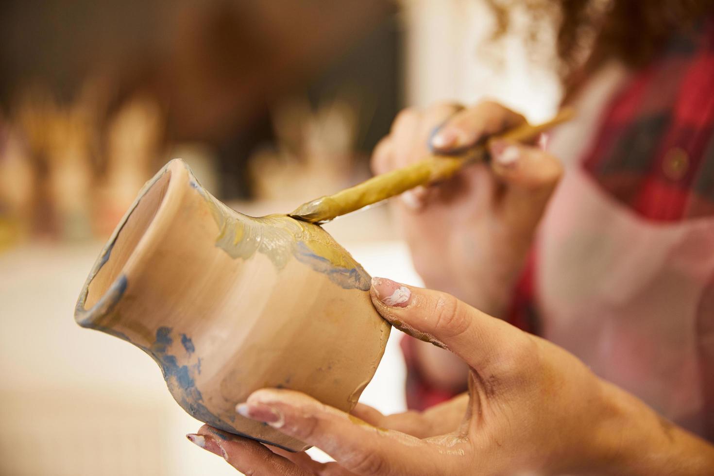 gros plan, la fille peint un vase avant la cuisson photo