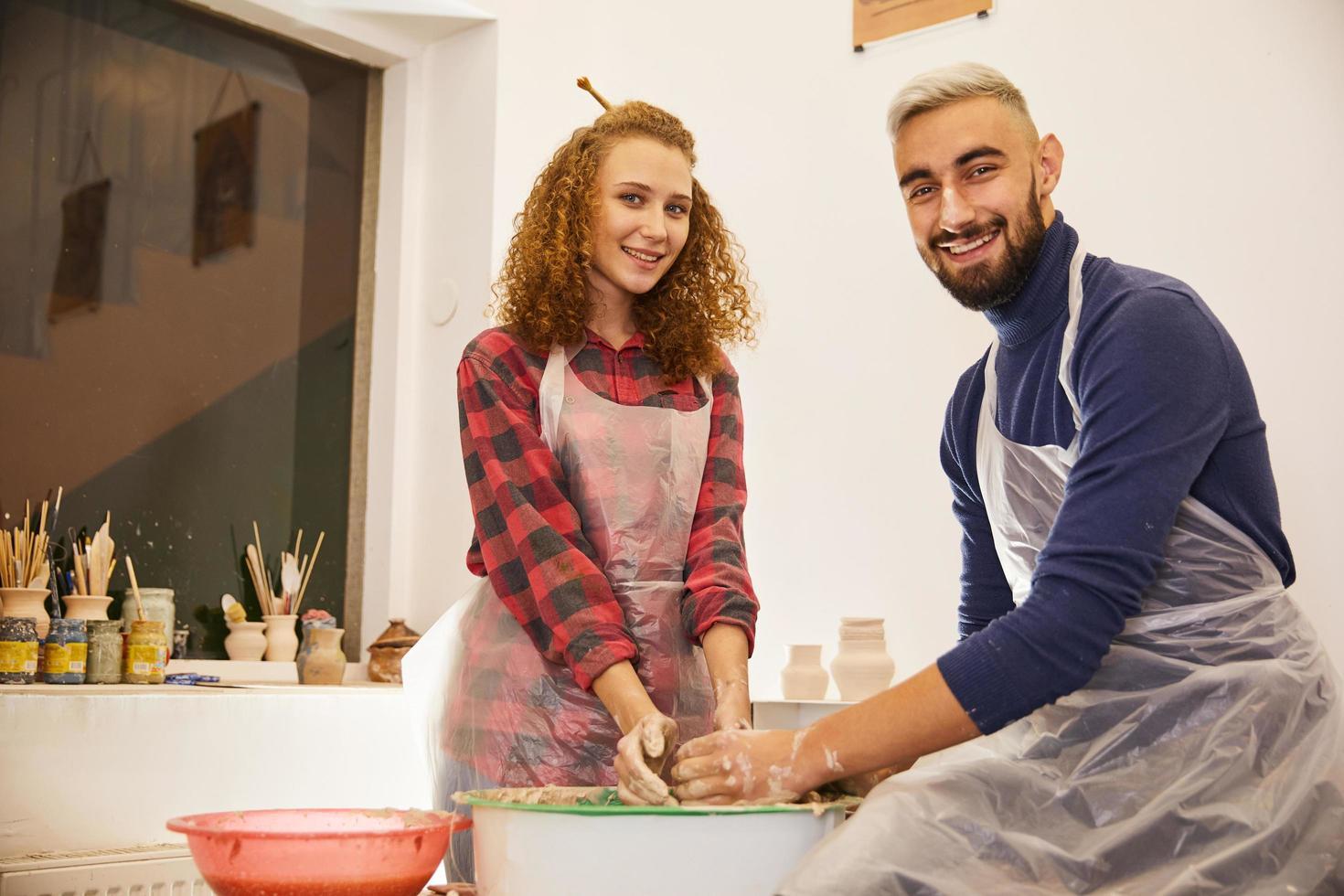 Beau couple souriant forme un vase dans un lieu de travail de poterie photo