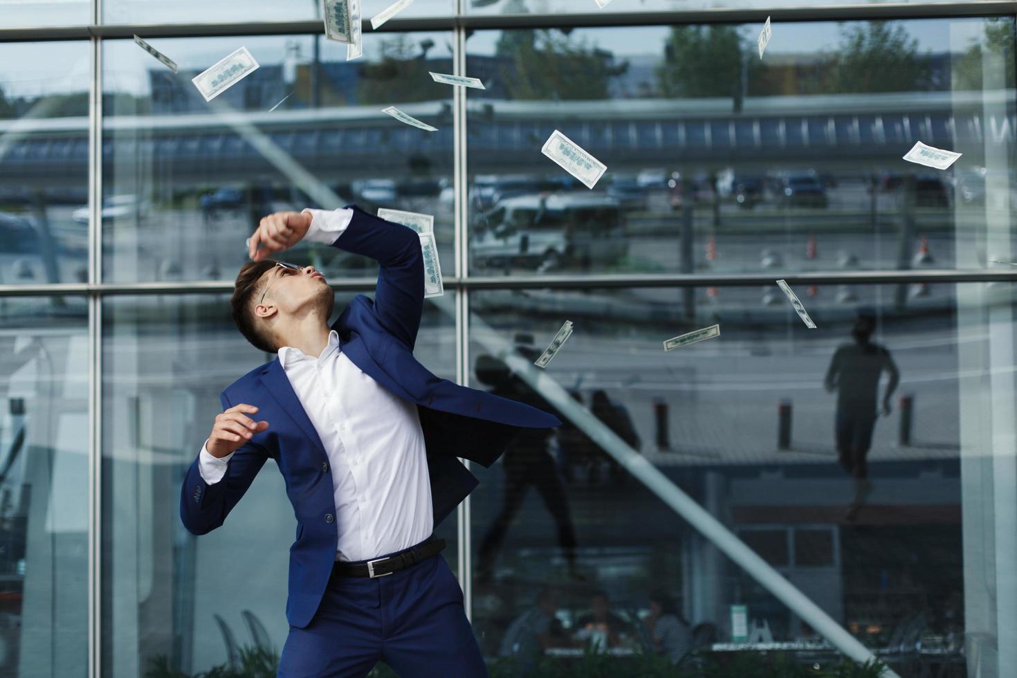 dollars volent autour de beau jeune homme d'affaires photo