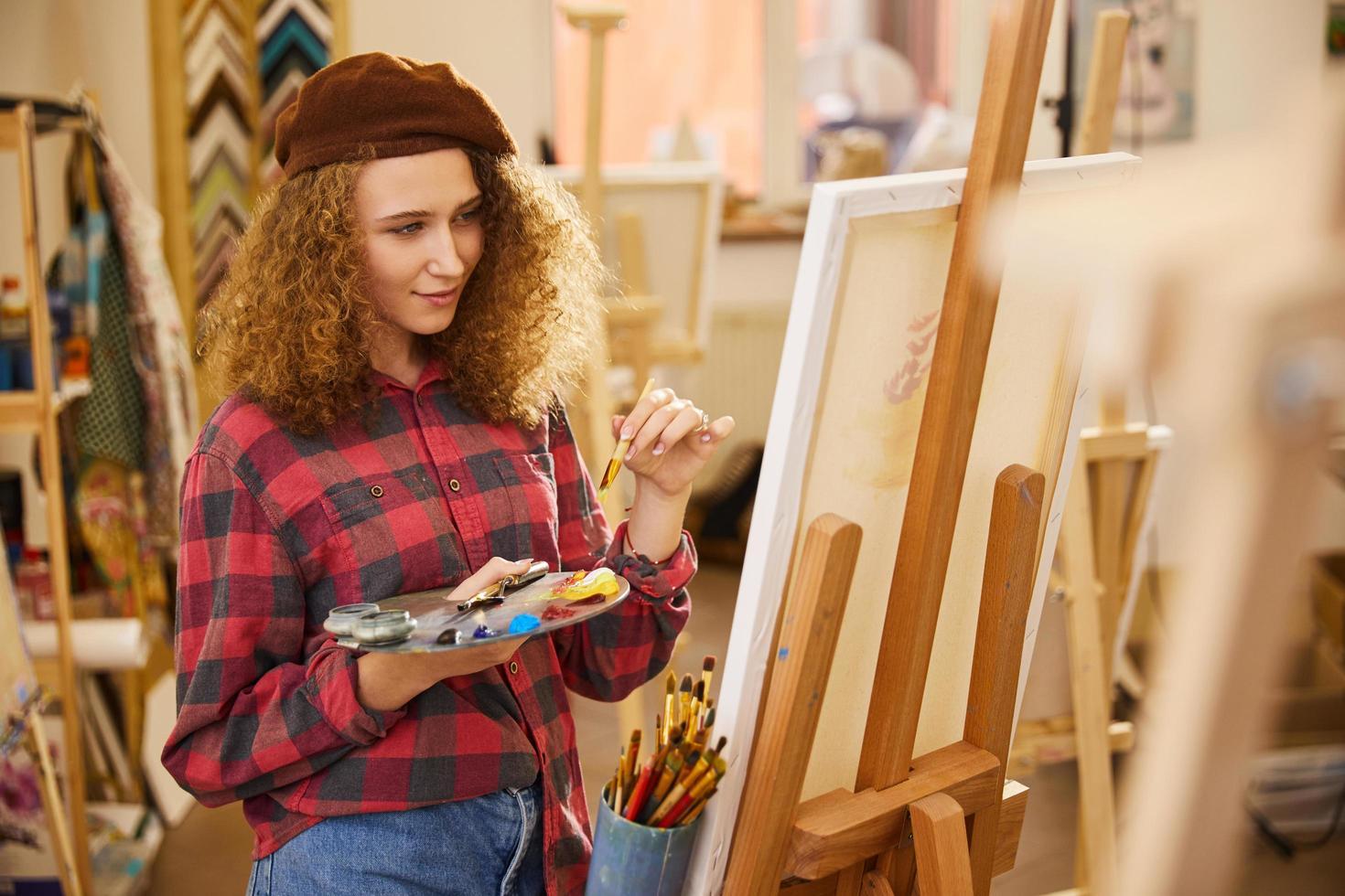 jeune fille tient une palette avec des peintures à l'huile et un pinceau photo