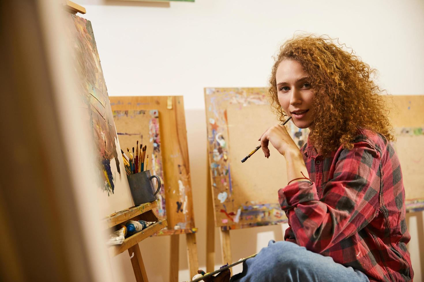 Portrait de la belle artiste bouclée rousse avec pinceau pendant son travail photo