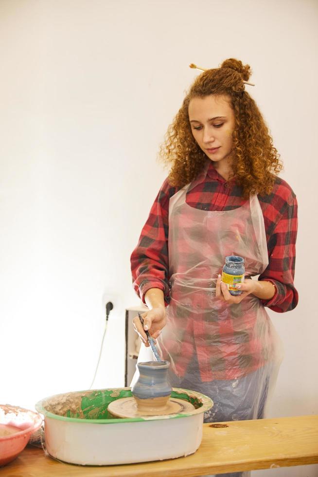fille rousse bouclée couvre un vase de poterie par une couleur bleue photo