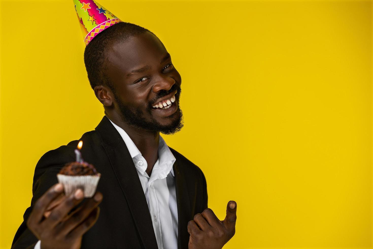 Heureux homme d'affaires mignon souriant à la caméra et tenant un gâteau d'anniversaire photo