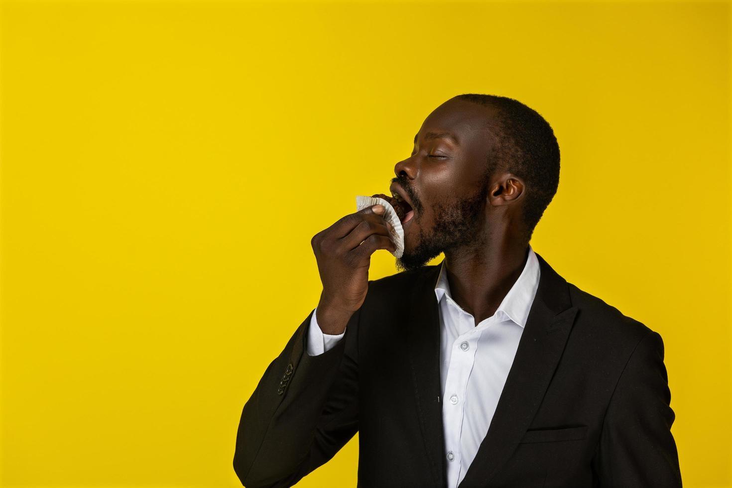 jeune homme mange un petit gâteau photo