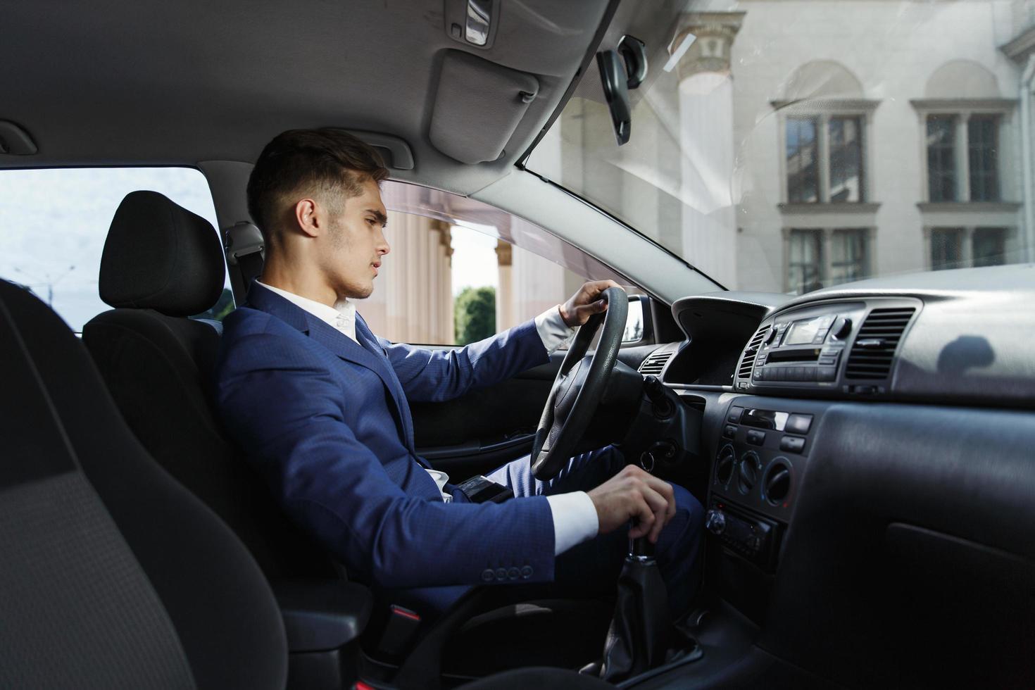 homme d'affaires souriant est assis à l'intérieur de la voiture photo