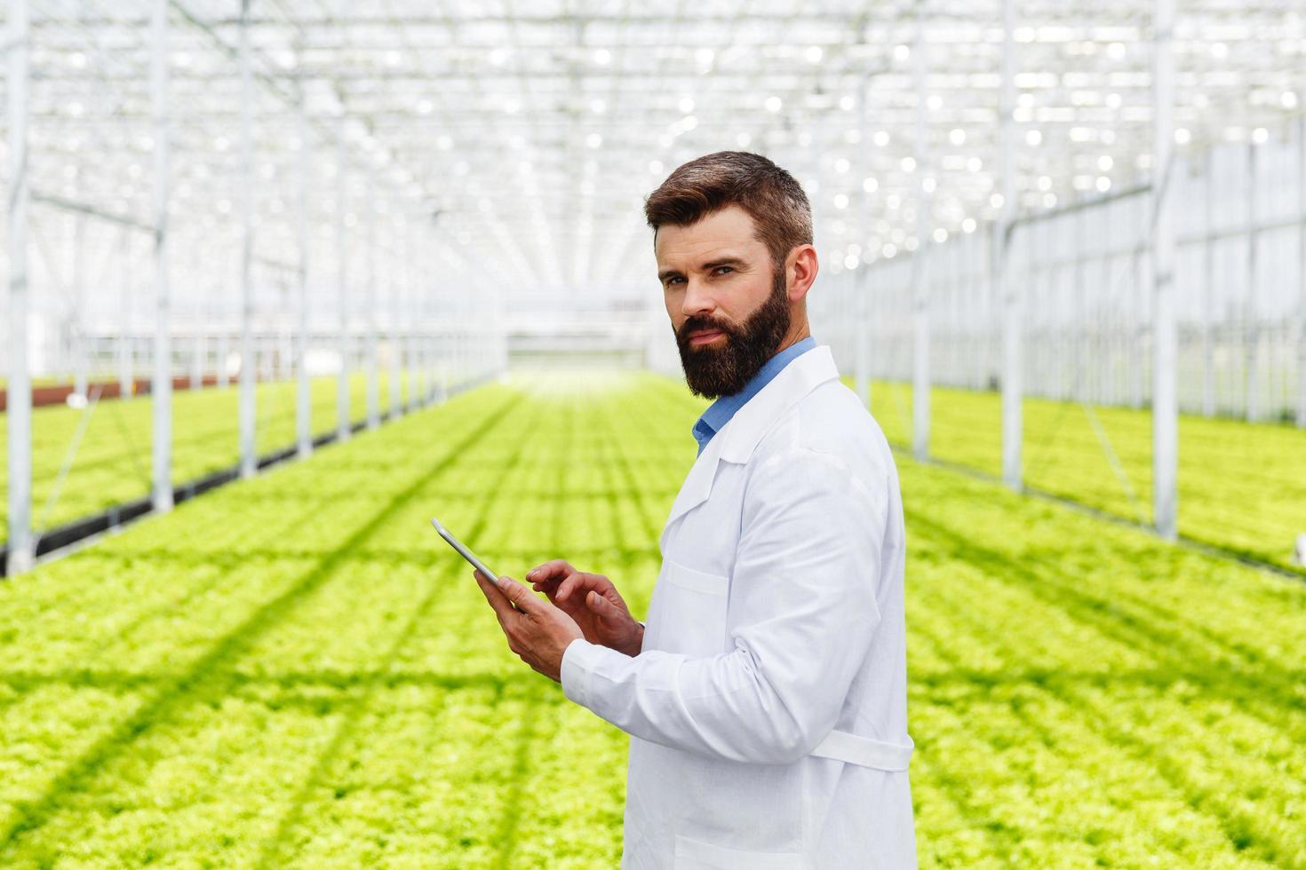 chercheur mâle étudiant les plantes avec une tablette photo