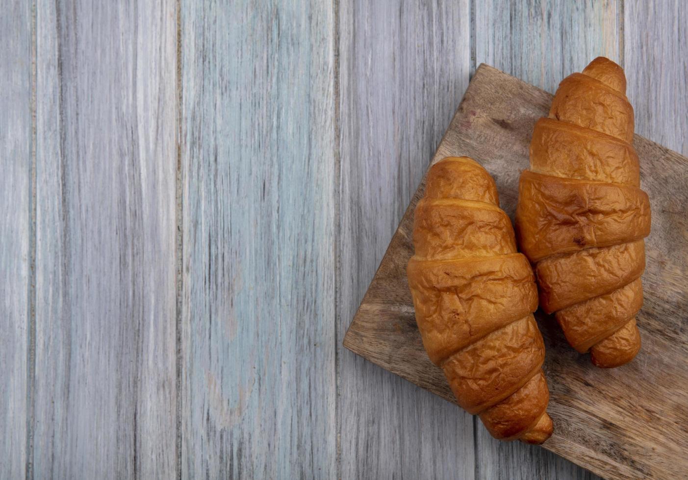 croissants sur une planche à découper sur fond de bois photo