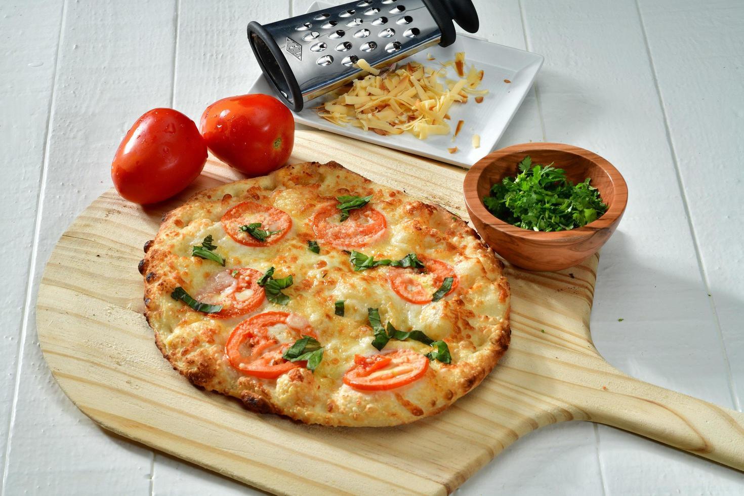Pizza cuite sur planche à pizza en bois brun photo