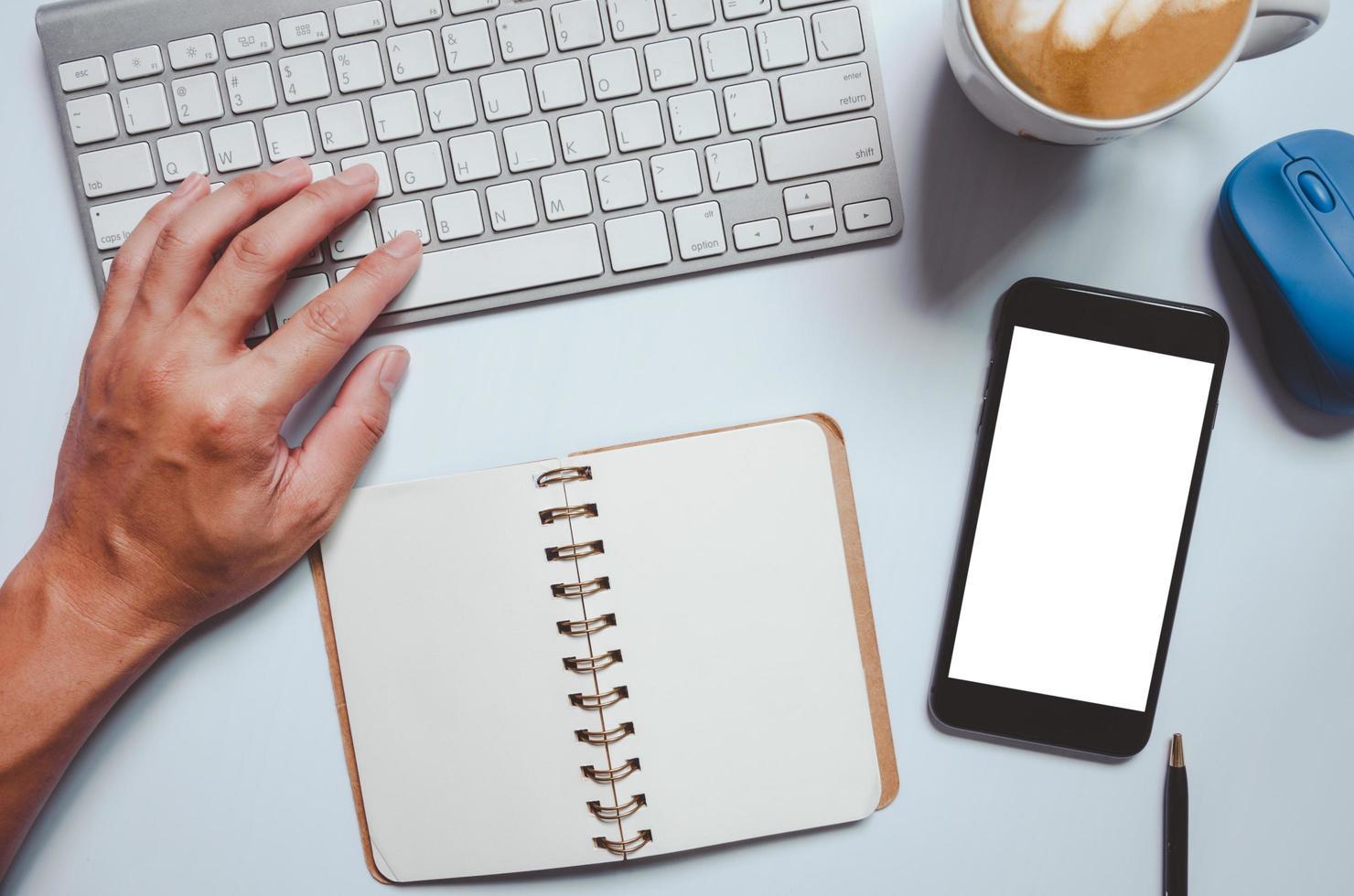 maquette de smartphone avec une personne travaillant sur ordinateur photo