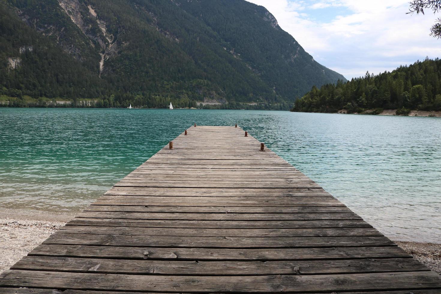 quai en bois menant à un lac pendant la journée photo