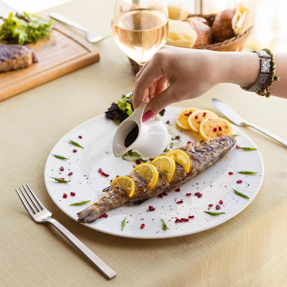 Femme verser la sauce sur un repas de poisson au citron photo