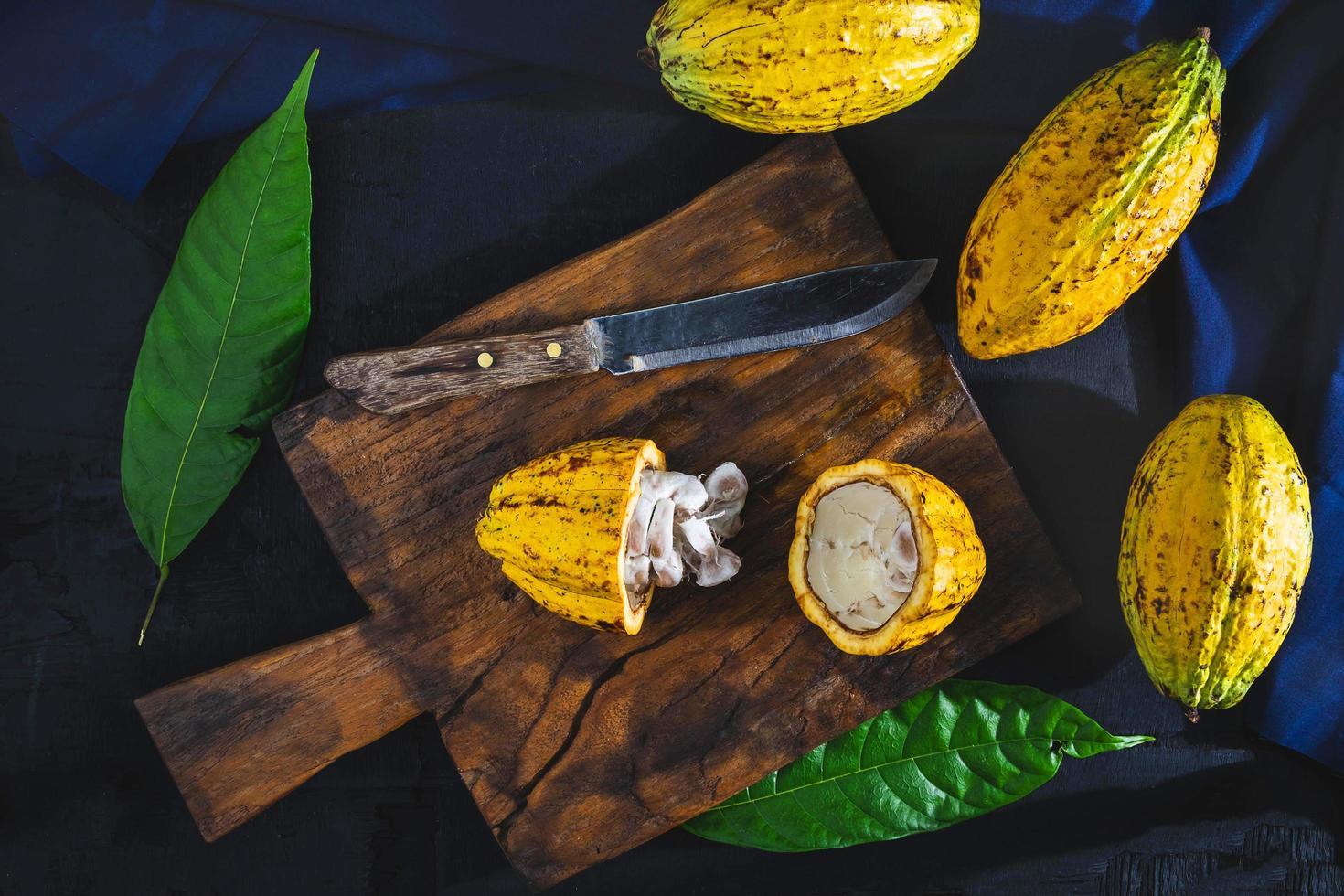couper les fruits de cacao sur une planche à découper en bois. photo