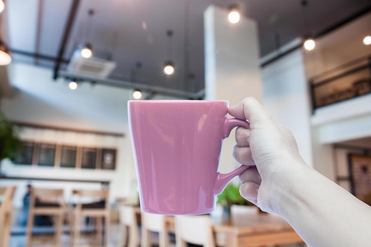 personne tenant une tasse de café photo