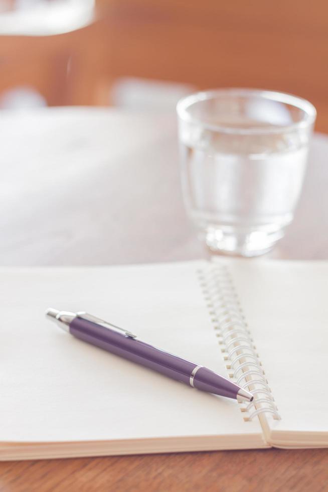 cahier et stylo avec un verre d'eau photo