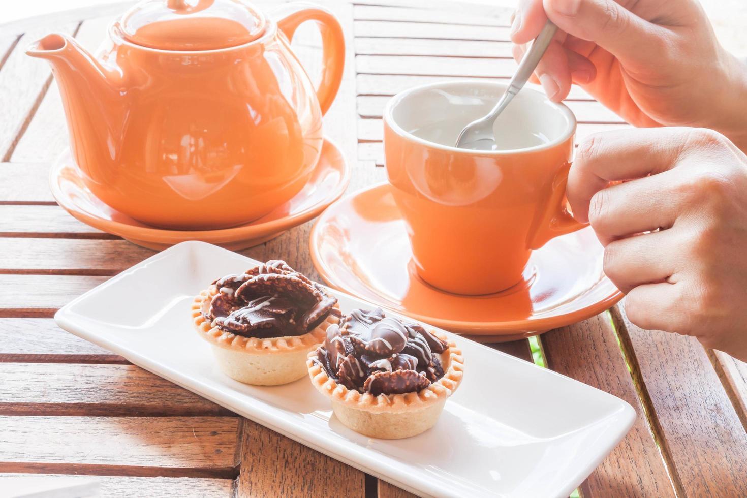 personne prenant du thé et des petits gâteaux photo
