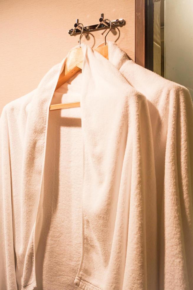 Robes blanches sur des cintres en bois dans un dressing photo