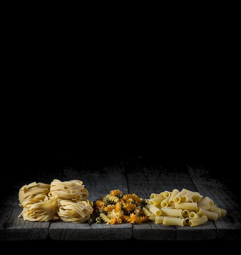pâtes fraîches sur bois devant un fond noir photo