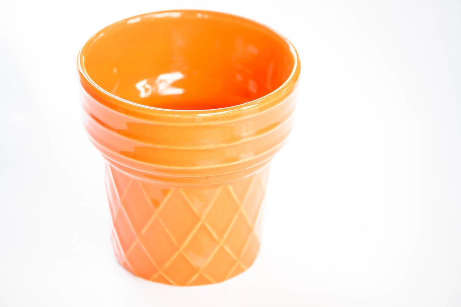 tasse orange sur fond blanc photo