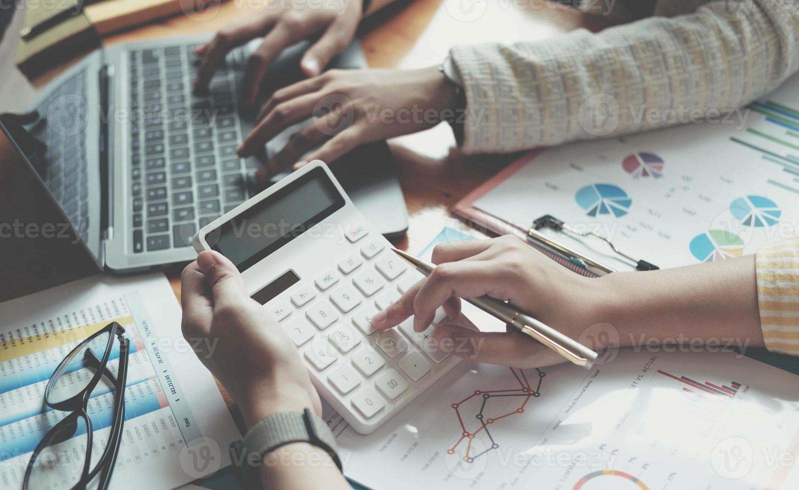 partenaires commerciaux utilisant une calculatrice et un ordinateur portable photo