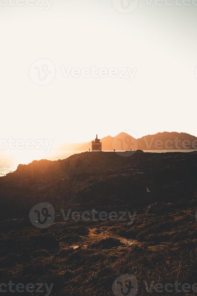 phare rouge sous un coucher de soleil massif photo
