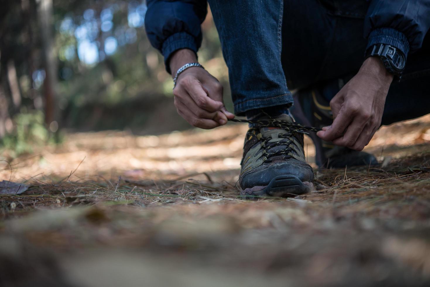 Homme jeune randonneur attache ses lacets de chaussures lors de la randonnée dans la forêt photo