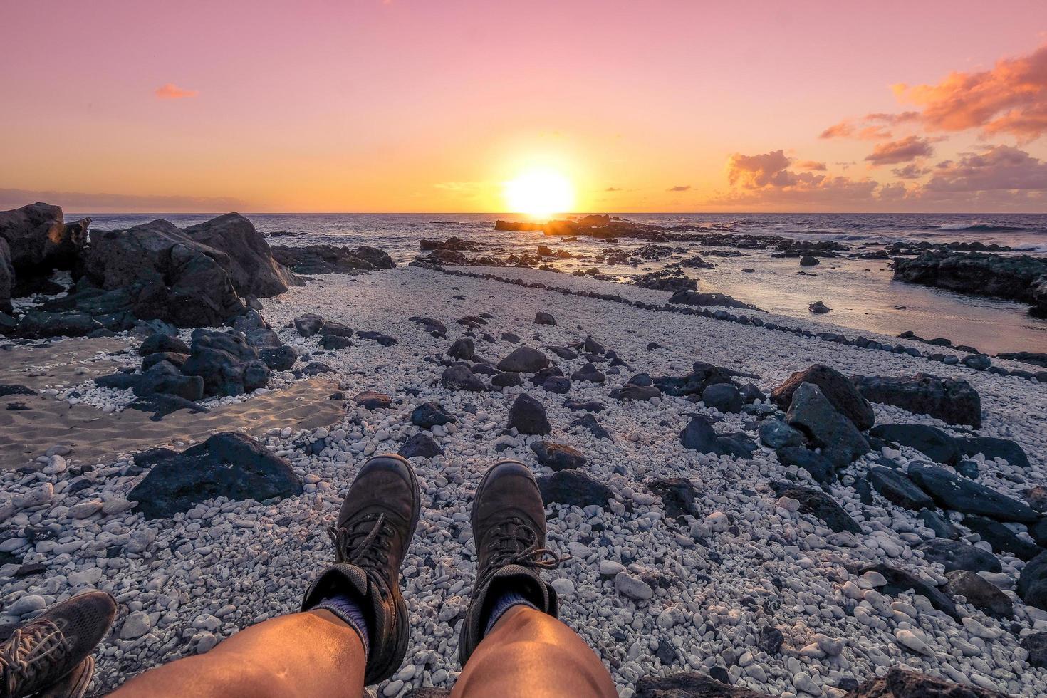 personne assise à la mer au coucher du soleil photo