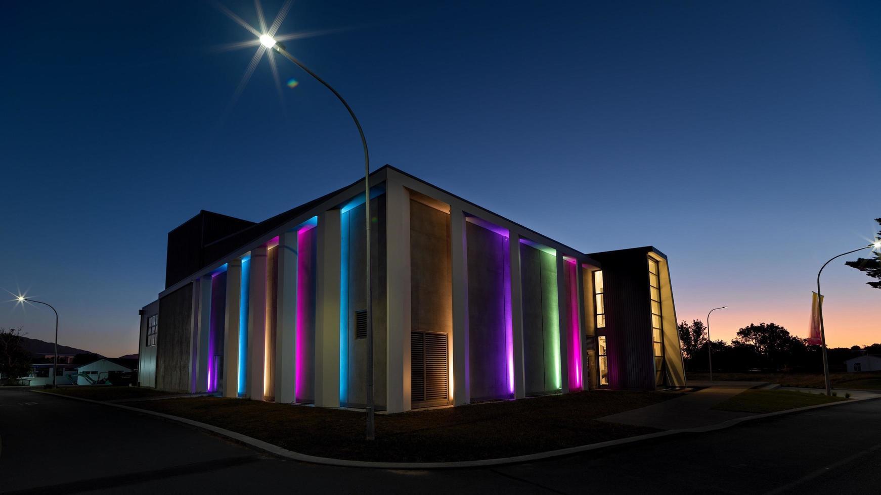 Bâtiment lumineux violet vert et jaune pendant la nuit photo