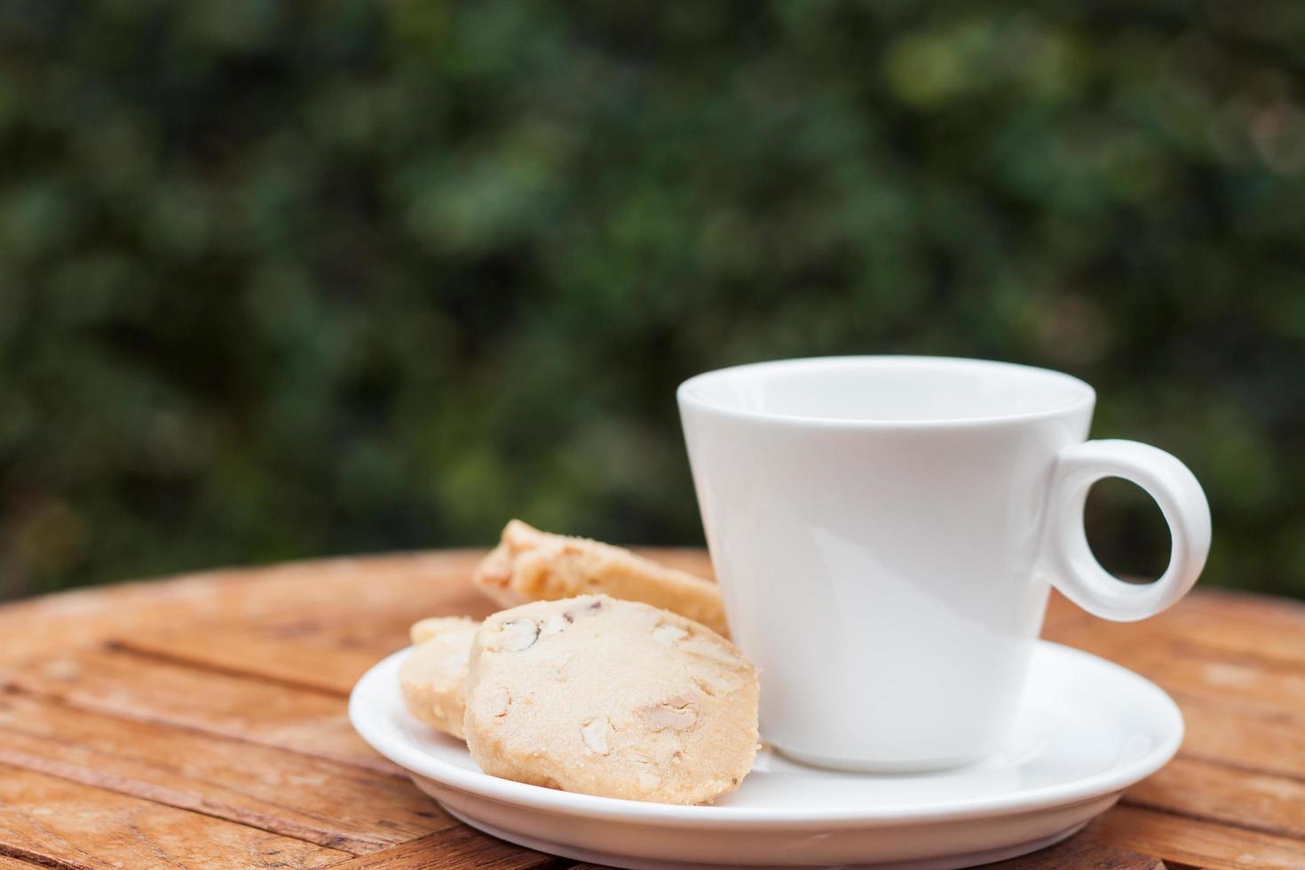 Biscuits aux noix de cajou avec une tasse de café blanche sur une table à l'extérieur photo