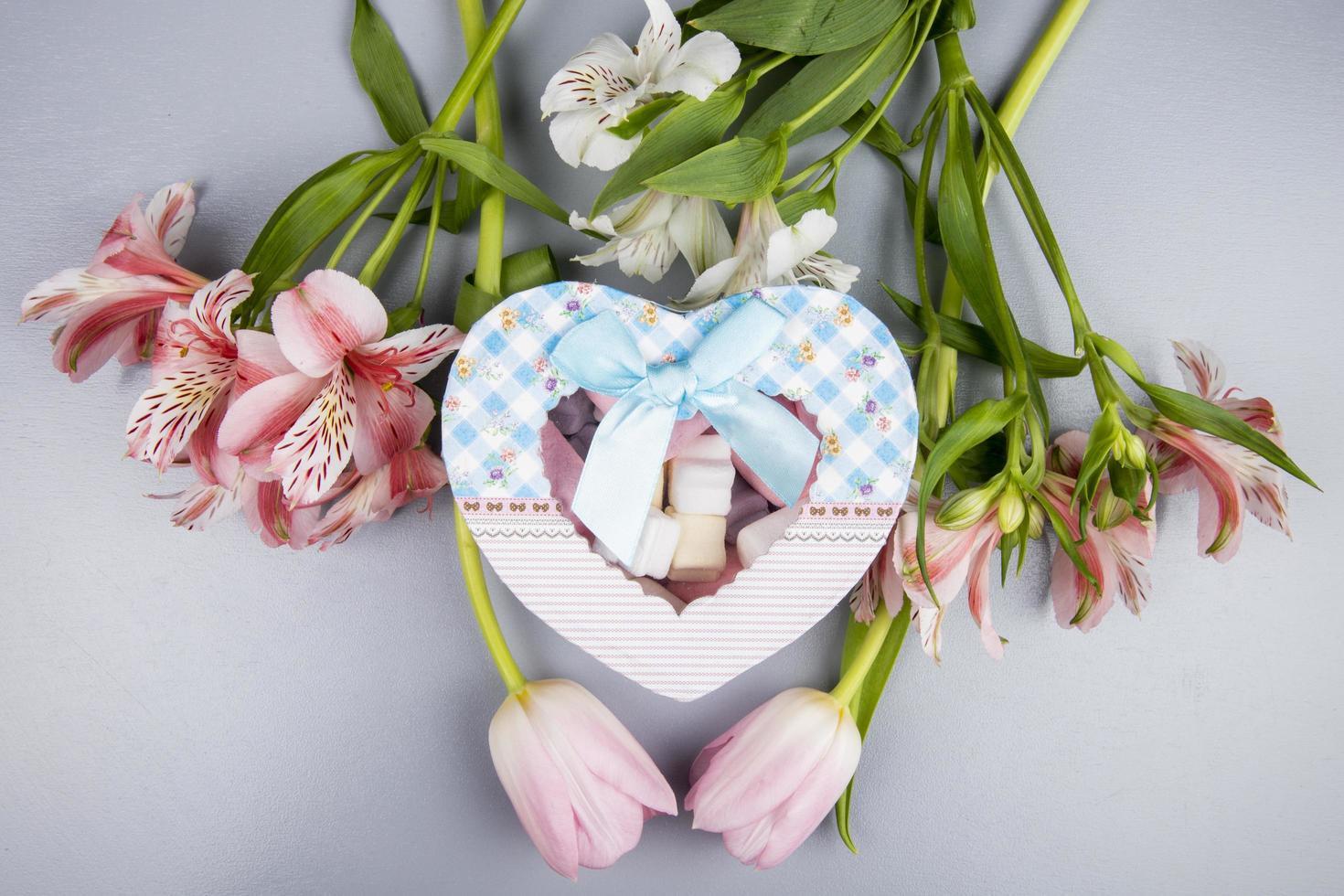 Vue de dessus d'une boîte cadeau en forme de coeur fleurs de tulipes photo